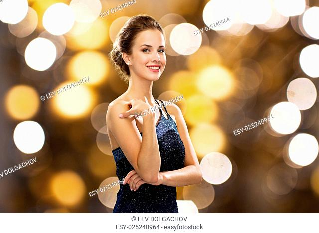 people, holidays, jewelry and luxury concept - smiling woman in evening dress and pearl earring over lights background