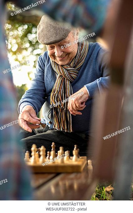 Senior man and grandson playing chess
