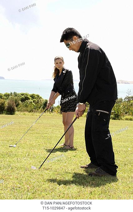 a man and a woman golfing