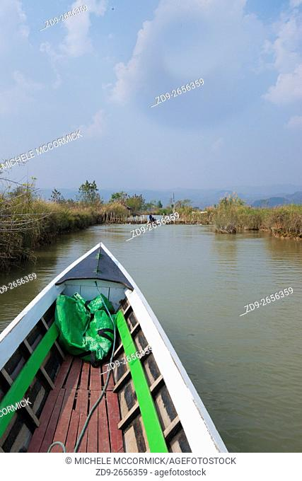 A boat makes its way along a narrow canal from Inle Lake to Indein