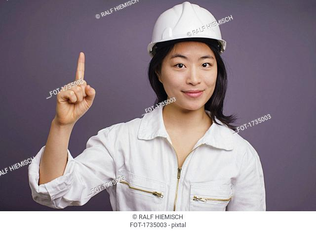 Portrait of confident young female construction worker wearing hardhat pointing up