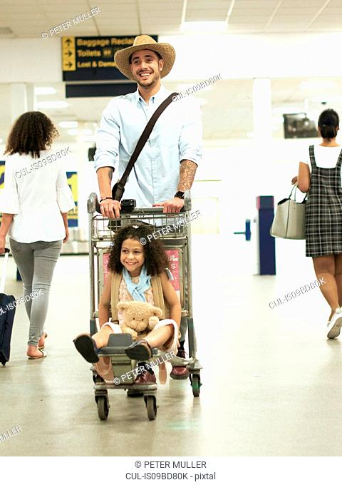 Father with girl on luggage trolley in airport