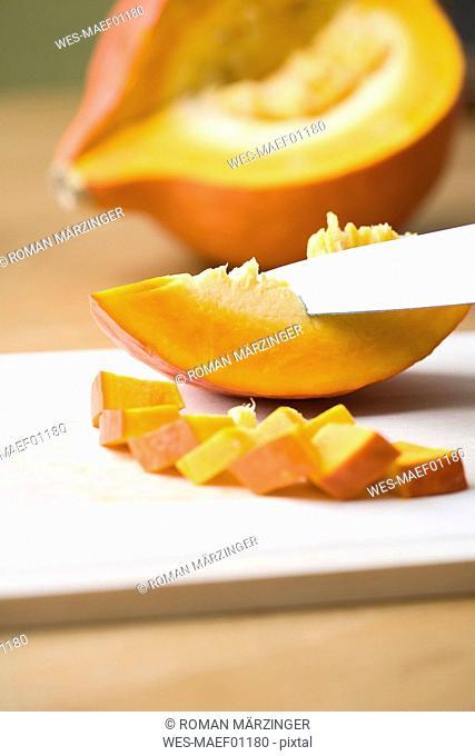 Knife slicing Hokkaido pumpkin, close-up