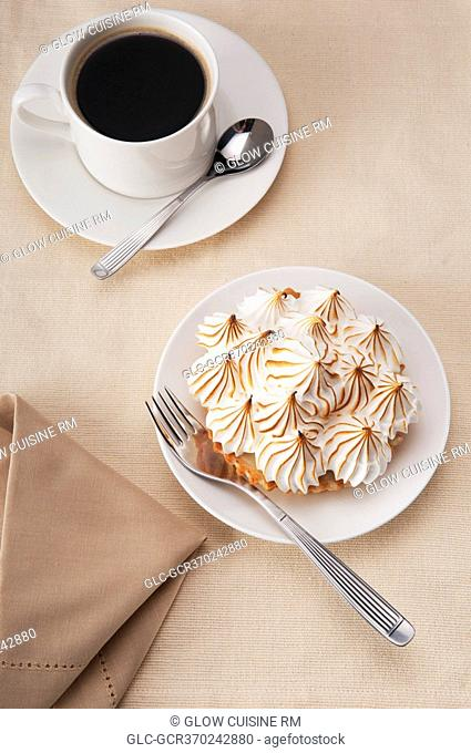 High angle view of a meringue pie with a cup of black coffee
