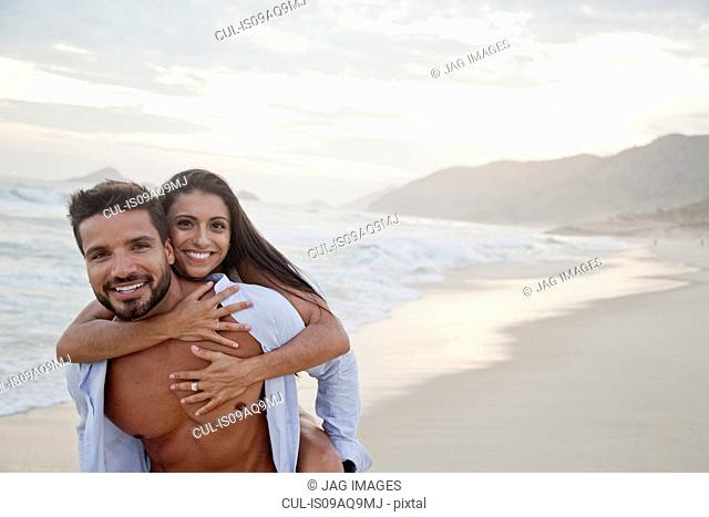 Portrait of mid adult couple on beach, man carrying woman on back