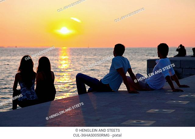 Couples relaxing on pier outdoors