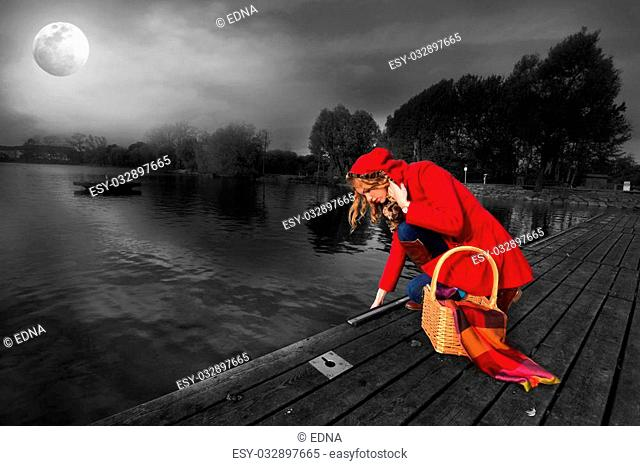 Beautiful girl in a red coat near the pond