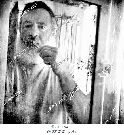 A man brushing his teeth in an old mirror