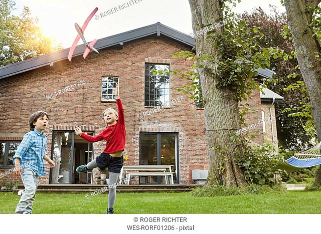 Two children playing with toy airplane in garden of their home