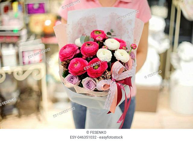 Girl in pink shirt holding in her hands a beautiful big bouquet of violet, white and pink tender flowers decorated with a bow
