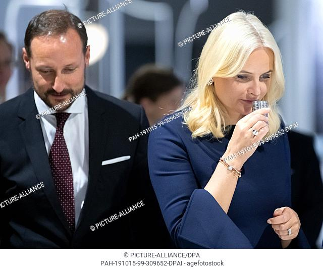 15 October 2019, Hessen, Frankfurt/Main: Crown Princess Mette-Marit of Norway smells an odour sample from an artistic installation while she and her husband