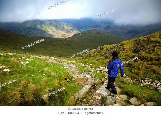 England, Cumbria, Lake District National Park, Lake District National Park. Hiker descending from tarn towards Dungeon Ghyll in the Great Langdale Valley