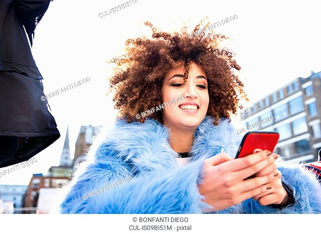 Portrait of woman with afro looking at smartphone smiling