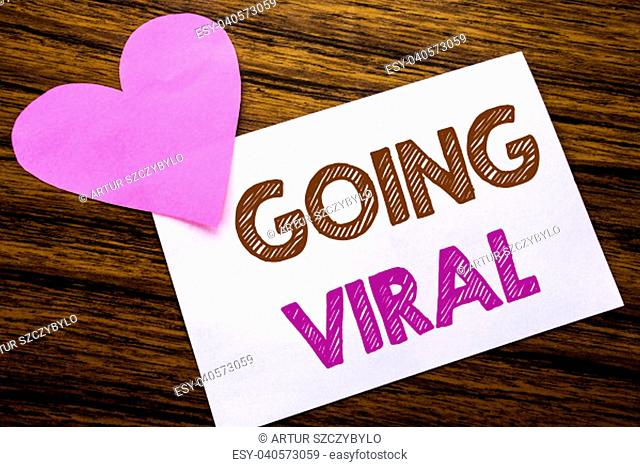 Conceptual hand writing text showing Going Viral. Concept for Social Viral Business written on sticky note paper, wooden background