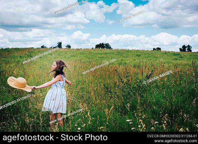 Teen Girl Twirling in a Grassy Field on a Cloudy Summer Day