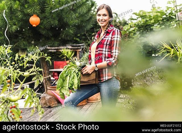 Smiling young woman carrying crate while standing in vegetable garden