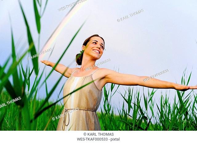 Happy young woman with outstretched arms standing in between reed