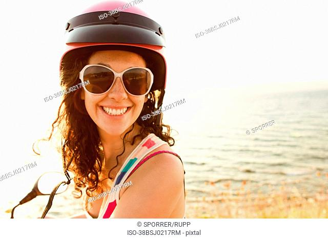 Smiling woman riding scooter on beach