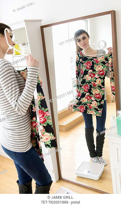 Young woman fitting dress in front of mirror