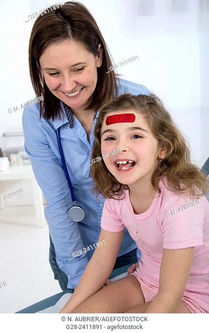 Pediatrist doctor and laughing little girl with a red dressing on her forehead