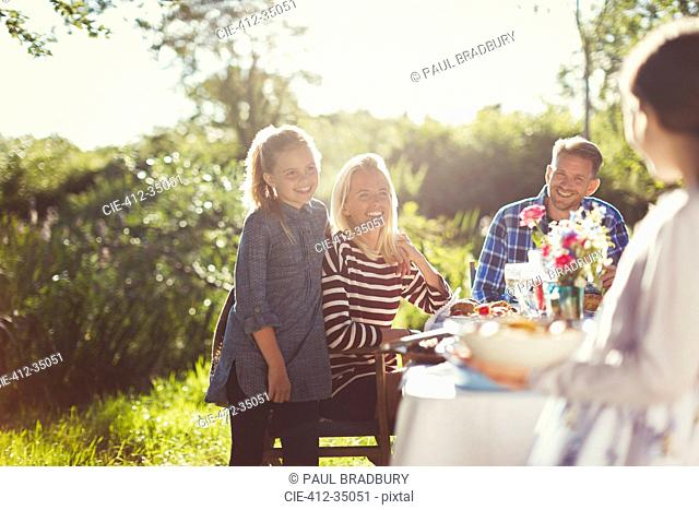 Happy family enjoying lunch at sunny garden party patio table