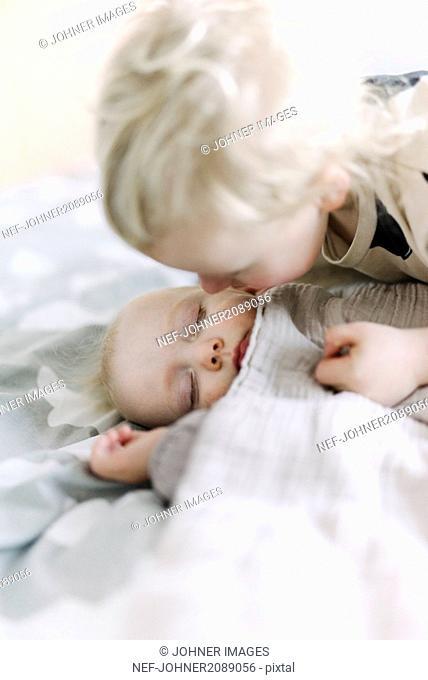 Sister kissing sleeping brother