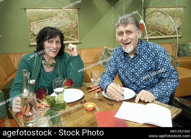 happy couple at dinner table with written plans
