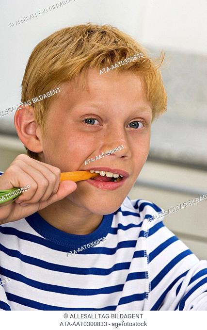 Boy nibbling carrot