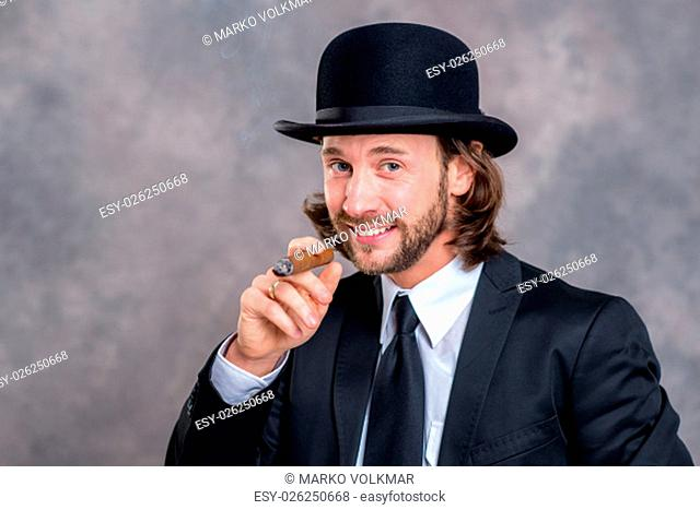 young businessman with bowler hat in black suit smoking big cigar