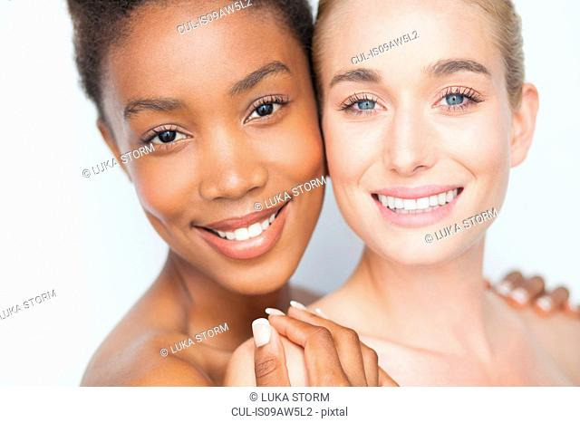 Woman with hands on friends bare shoulders looking at camera smiling