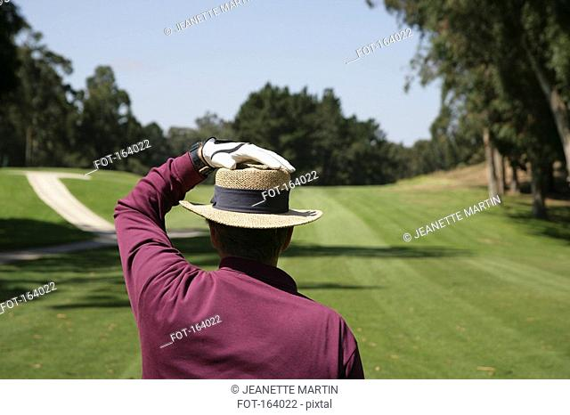 Rear view of a golfer after hitting a ball