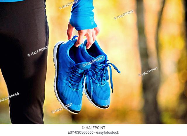 Unrecognizable runner in blue sweatshirt holding pair of sports shoes outside in colorful sunny autumn nature