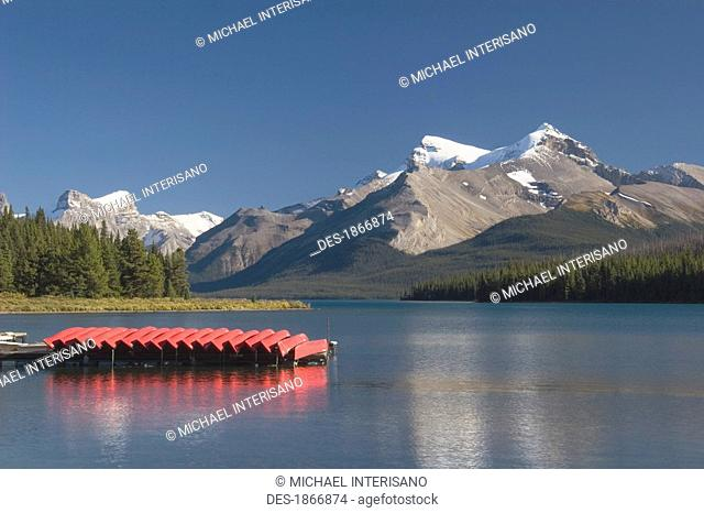 jasper national park, alberta, canada, canoes and a dock and mountains in maligne lake