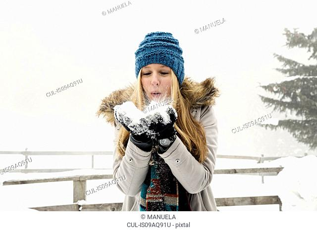 Young woman blowing handful of snow