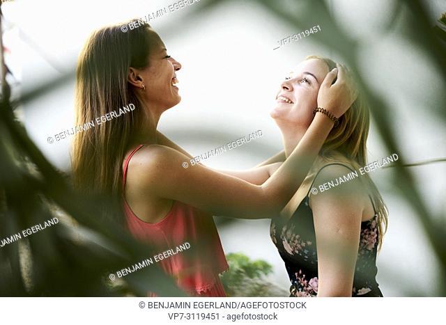 two women behind leaves