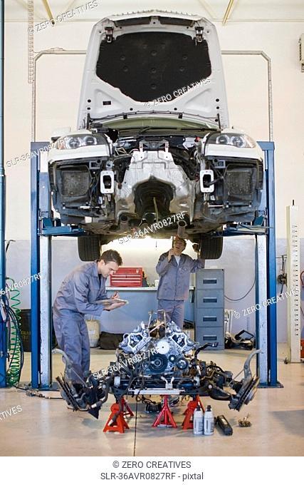 Mechanics working on car in garage