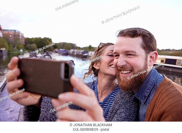 Couple taking selfie on canal boat