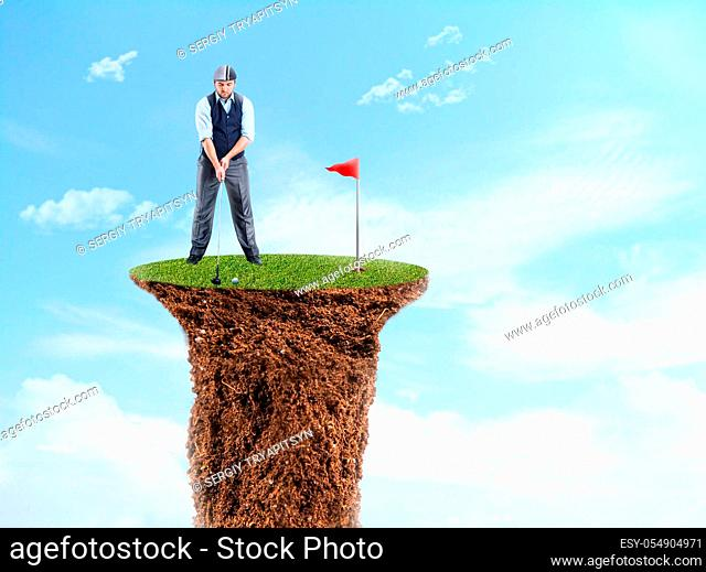 Businessman playing golf on the top of a grass cliff