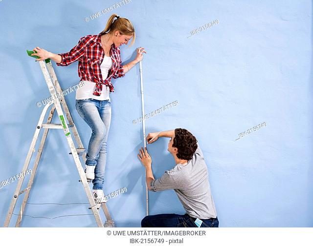 Young couple measuring a wall