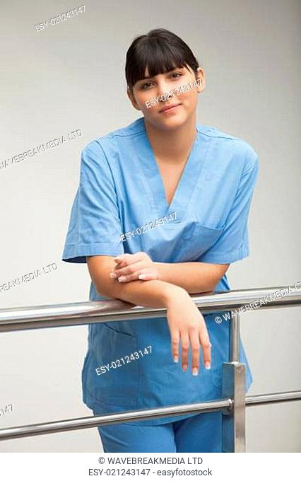 Content nurse leaning against railing in hospital corridor