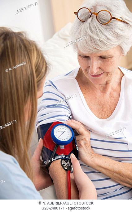 Doctor or nurse testing blood pressure with a blood pressure gage, on a beautiful senior woman at home or in clinic or hospital