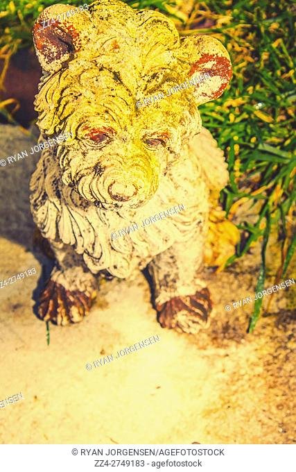 Cute weathered white garden ornament of a shaggy long-coated dog staring thoughtfully down at the ground while sitting alongside the grass, high angle