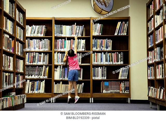 Girl reaching for book on library shelf