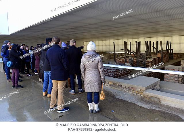 Visitors look at the remains of a crematorium at 'Station Z' at the Sachsenhausen concentration camp in Oranienburg, Germany, 27 January 2017