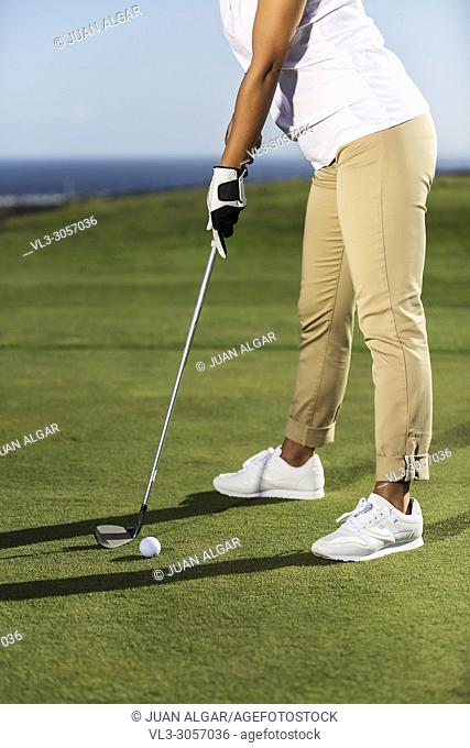 Faceless shot of woman in elegant outfit standing with driver in hands playing golf and driving ball