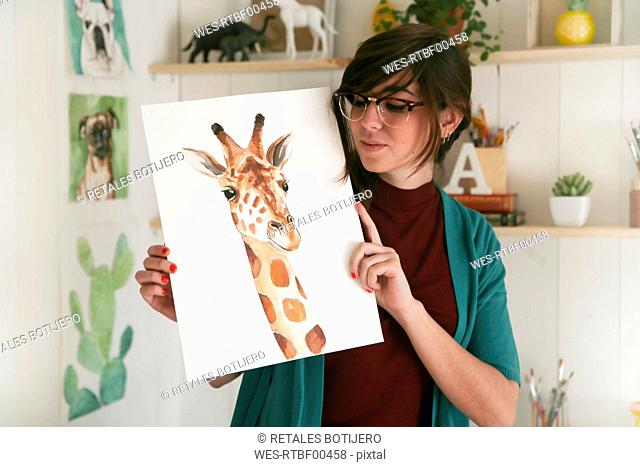 Portrait of artist showing her aquarelle of a giraffe