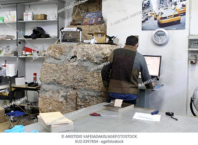 Ancient wall inside the large photocopy shop. Athens ancient walls. The Themistoklean wall surrounds Athens like a historical chain