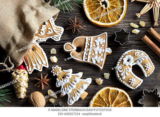 Christmas decoration - a linen bag with decorated gingerbread cookies, straw ornaments, star anise, walnuts, cinnamon, frankincense resin and dried orange...