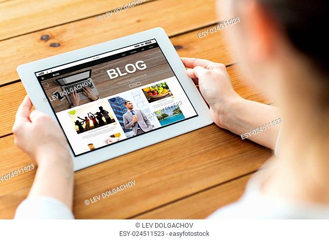technology, media, internet and people concept - close up of woman with blog web page on tablet pc computer screen on wooden table