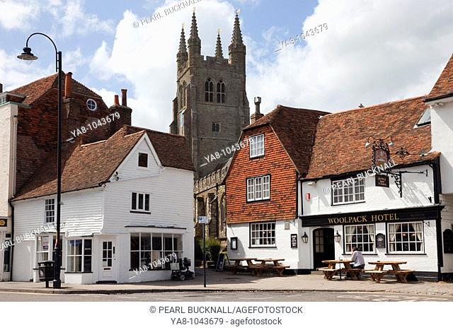 Tenterden, Kent, England, UK, Europe  The Woolpack hotel 15th century pub exterior and St Mildred's Parish Church clock tower in small historic Wealden town